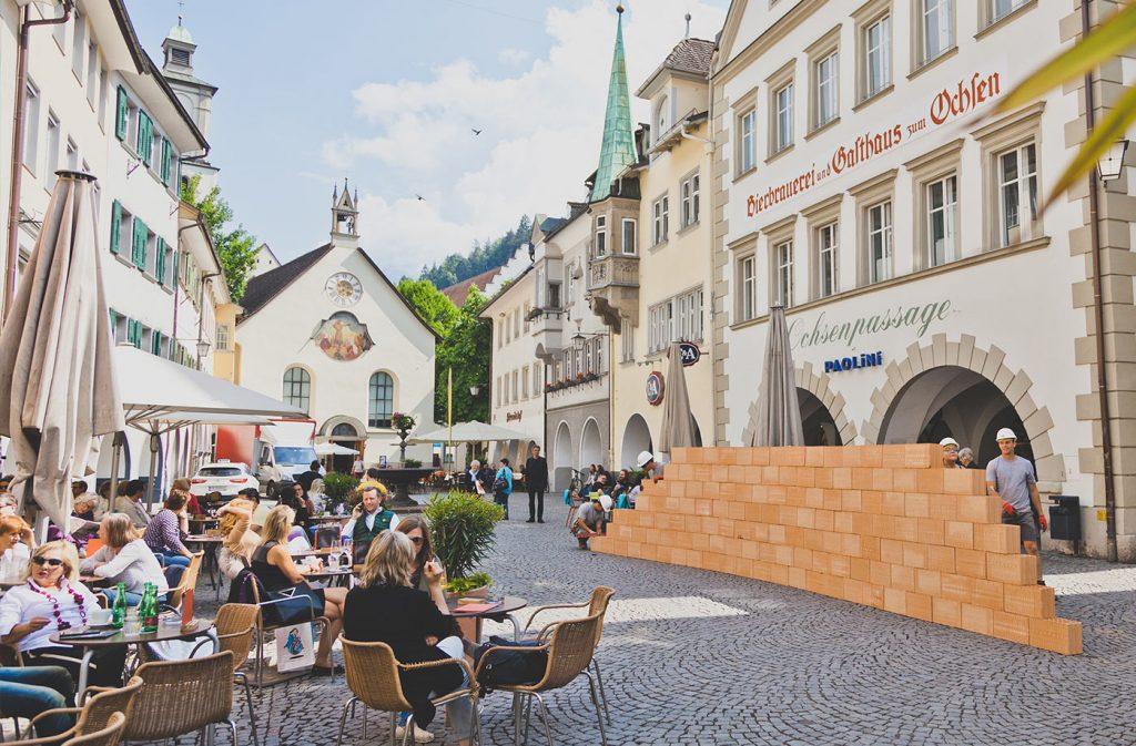 Glaser/Kunz, Wandernde Mauer (2018) in der Feldkircher Marktstraße, Johanniterkirche Feldkirch.